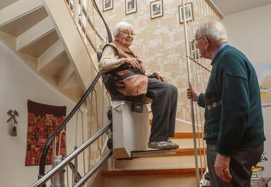 Ehepaar freut sich über Treppenlift mithilfe der Pflegestufen.
